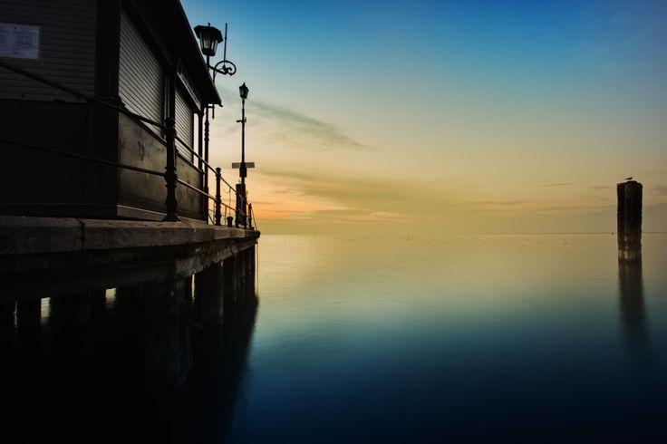 Molo sul lago by G. Bartuccio  - Scorcio al tramonto del molo di un paesino sul lago di Garda. Foto realizzata durante un tour caratterizzata dalla particolare  colorazione dovuta al momento. Paesaggio rilassante e riflessivo, dolce e malinconico. La quiete surreale del momento lascia allo spettatore la possibilità di volare con la fantasia.