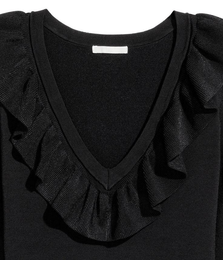 Siyah. Viskoz karışımlı parlak iplikten ince triko kazak. Fırfırlı derin V yakalı, uzun kollu.