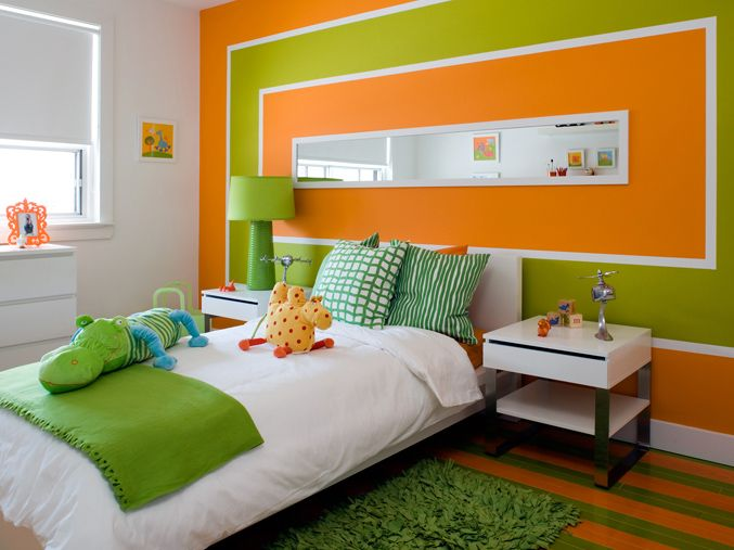 orange & green boy's bedroom design with orange & green painted striped floors, faux green grass rug, white platform bed, green throw blanket, green geometric throw pillows, modern white nightstands, green lamp, green & orange painted accent wall and Ikea furniture.