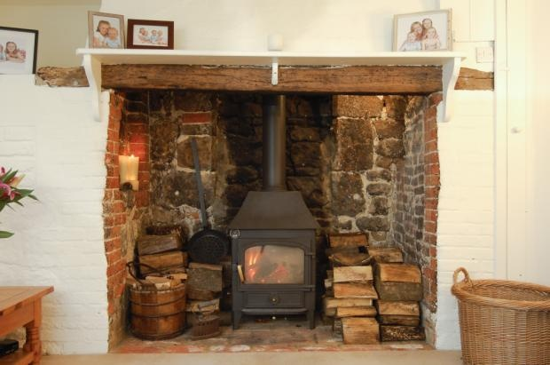 I can almost feel the heat coming off this lovely stove with very rustic surround