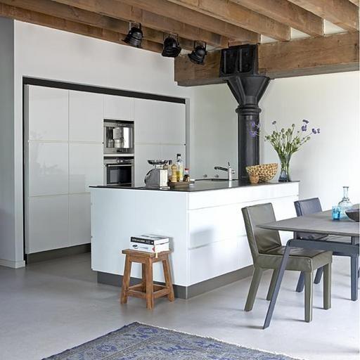 Deze moderne strakke keuken en de betonvloer vormen een groot contract met de oude houten balken aan het plafond en de industriële lampen.