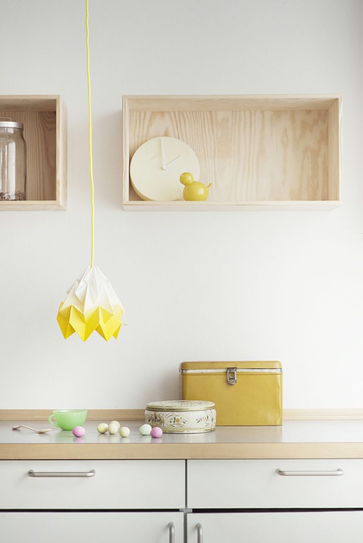 Snowpuppe origami lamp Moth small in a white and yellow interior setting with wood. Styling by @imogenwood