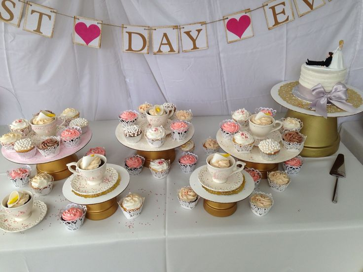 Our wedding cupcakes. We played on the lily theme (bride and groom's last name) by placing lily cupcakes in teacups. Clay pots were spray painted gold and topped with a cardboard cake board. Best day ever sign and wedding server purchased from etsy.     https://www.etsy.com/listing/194172068/best-day-ever-wedding-banner-engagement?ref=hp_mod_rf    https://www.etsy.com/listing/198849697/best-day-ever-hand-stamped-cake-server?ref=hp_mod_rf