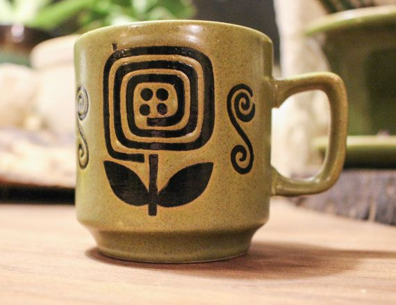 Very cool avocado green coffee cup with a black spiral flower. Its in very good shape, no chips. There is a flawed spot on one of the flowers, but its not damaged. This coffee cup would make a great addition to anyones cup collection.