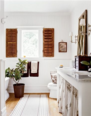 these shutters are perfect against the white beadboard walls. love the vanity, mirror and rug also