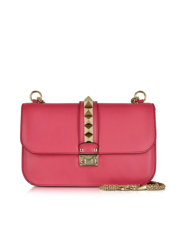 Deep Fuchsia Medium Chain Cross Body Bag crafted in lightly textured calf leather, is a statement bag with a pop of flair. Featuring flap top with Tuc lock closure and logo detail, adjustable chain shoulder strap, interior zip pocket, double open pocket, signature platinum finish pyramid studs and gold tone hardware. Signature dust bag included. Made in Italy.