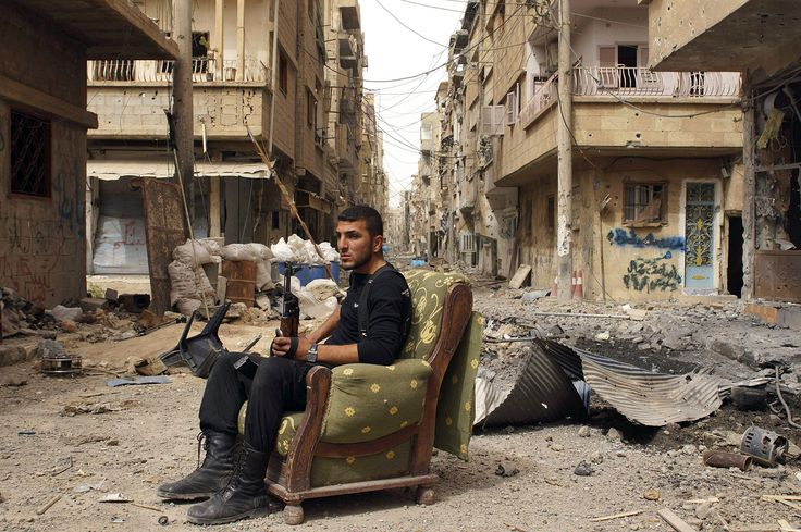 A member of the Free Syrian Army sits on a sofa in the middle of a debris-strewn street in Deir al-Zor, Syria, on April 2, 2013