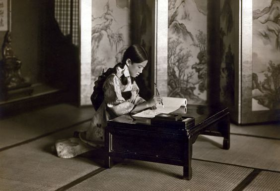 A young Japanese girl writes at her desk. Photo courtesy of UNSM Archives.