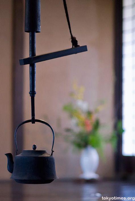 Japanese iron tea kettle (tetsubin) hung on a jizaikagi.