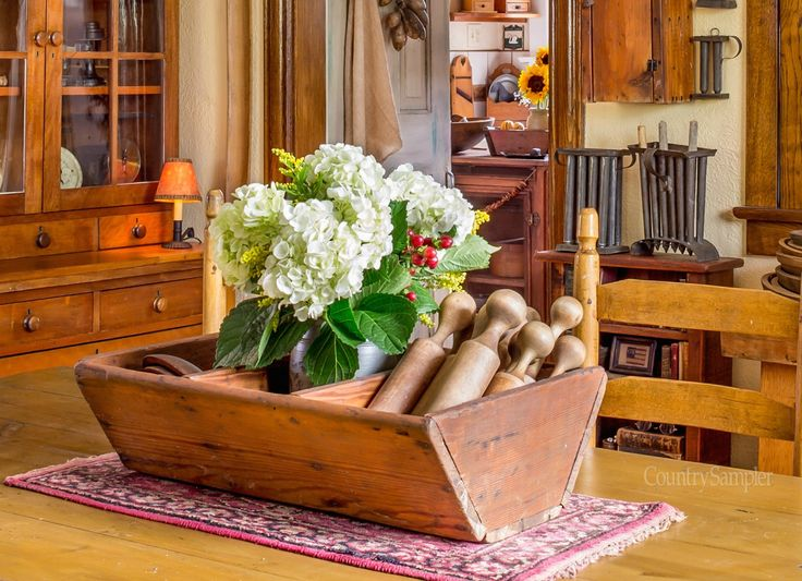 Place a potted plant amid collectibles in compartmentalized wooden trough.