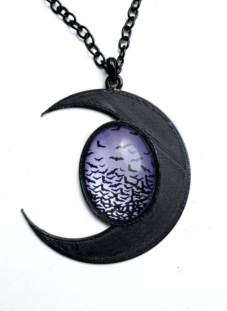 """This stunning large moon necklace is made from a 3D printed setting. It measures approximately 3x3"""" A glass cabochon with black bats flying amidst a purple metallic background sits in the center of the moon. It hangs on a 22"""" black chunky chain. If you would like the bats in a different colored..."""