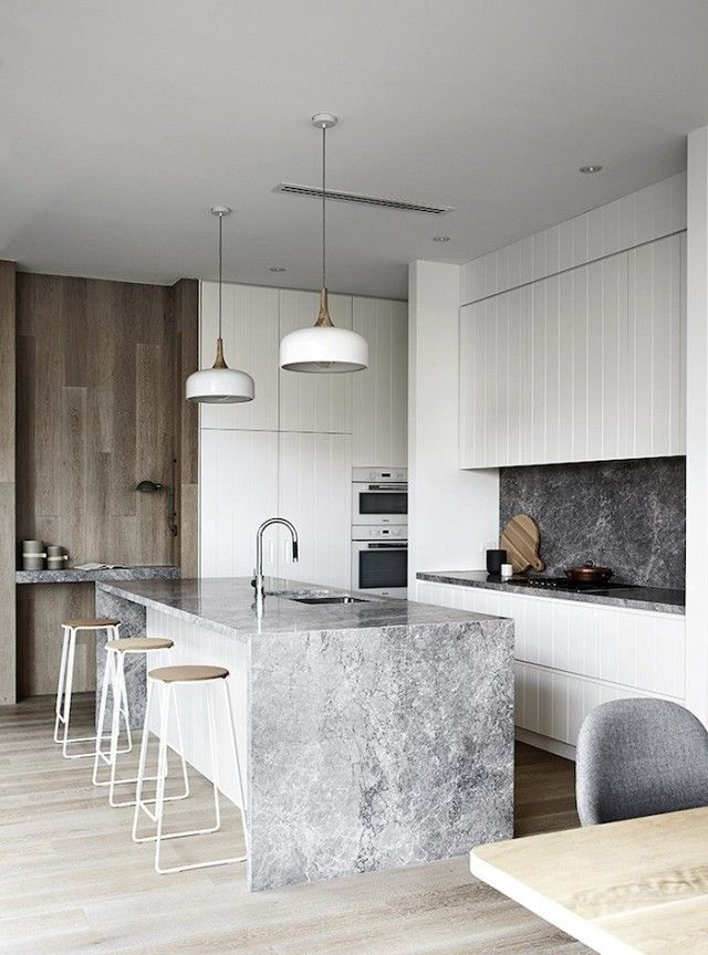 Modern kitchen with a marble island, modern pendant lights, and white cabinets