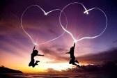 jong stel springen en tekenen verbonden harten door zaklamp in de lucht op het strand voor zonsopgang stock photography
