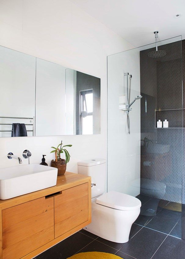 """The custom-made timber vanity is teamed with a Kohler basin and a mirrored shaving cabinet, both from Harvey Norman, and a Porcher""""Cygnet' toilet suite from Reece"""