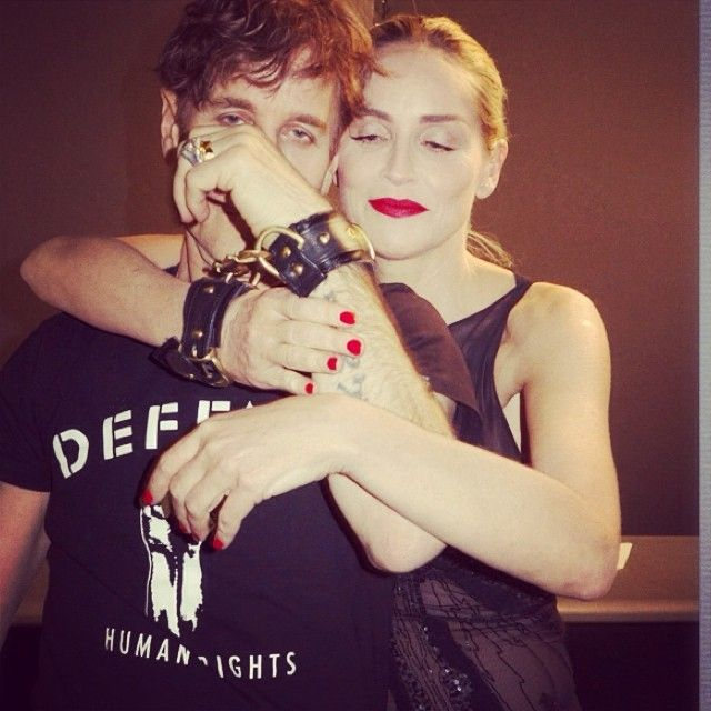 Behind the scenes image of Sharon Stone and Steven Klein binded by the Model Traitor Cuffs