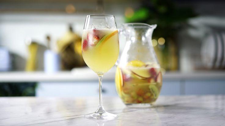 Receita com instruções em vídeo: Leve, refrescante e colorido, o Clericot combina super bem com o clima de Carnaval!   Ingredientes: ½ laranja em fatias, ½ maçã vermelha em fatias, ½ maçã verde em fatias, 1 kiwi picado, ½ xícara de uva, ½  xícara de morango picado, ½ copo de cointreau (licor de laranja), 2 xícaras de melão picado, Água, Gelo, 1 garrafa (750ml) de vinho branco seco