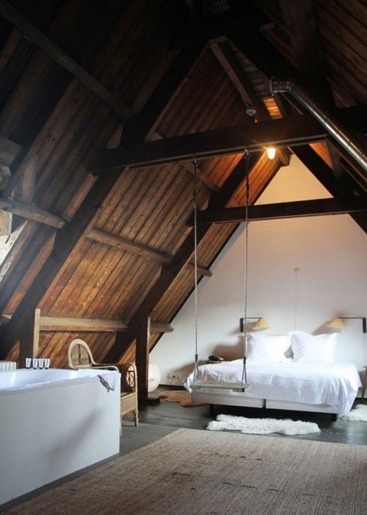 An attic bedroom at the Lloyd Hotel in Amsterdam, complete with swing.