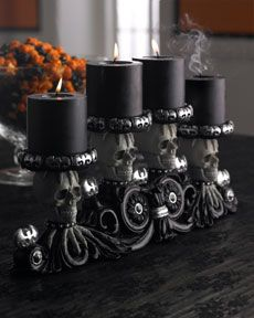 Decorative holder for four candles, black with skulls.