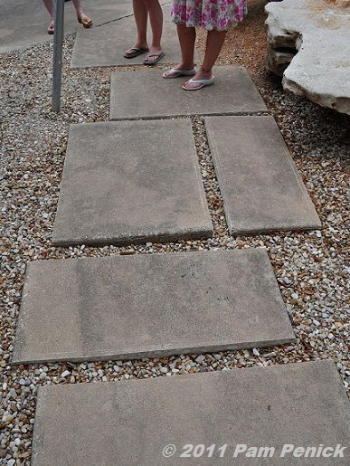A plain concrete walk cut into mosaic pieces and re-laid in a bed of pea gravel for an interesting visual detail.  A concrete cutter can be rented...