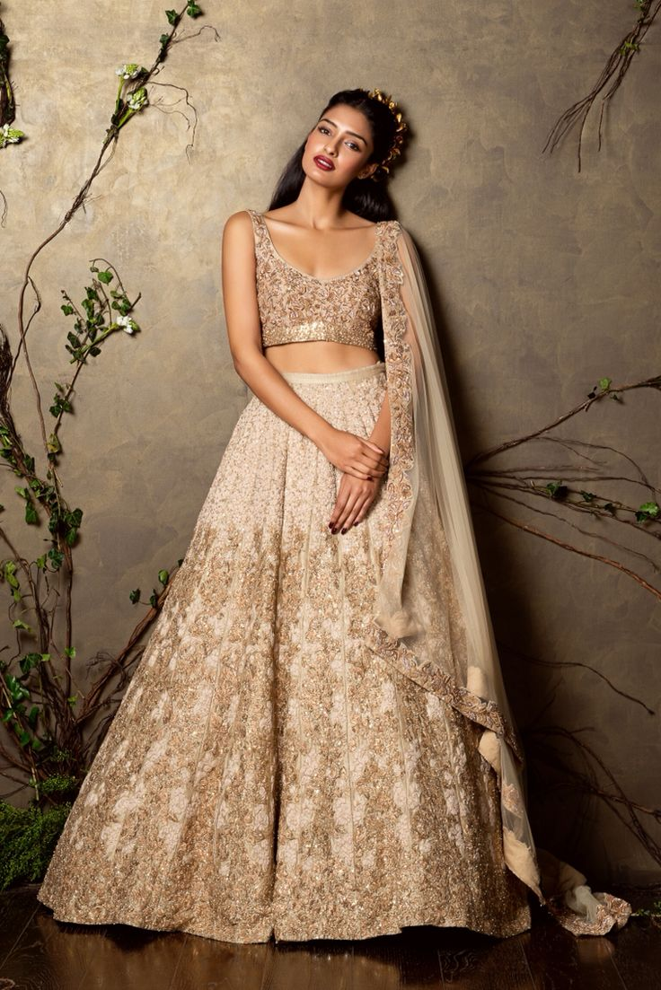 A panelled almond beige raw silk lehenga with diffused thread and beaten zari work. This is teamed with a gold encrusted choli and tulle dupatta with a khaat work border and blobs of shimmer all over add understated glamour to the outfit.   Sales@shyamalbhumika.com   www.shyamalbhumika.com