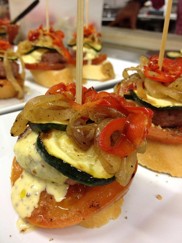 Montadito de tomate, hamburguesa de ternera, calabacín, pimientos, cebolla y salsa.