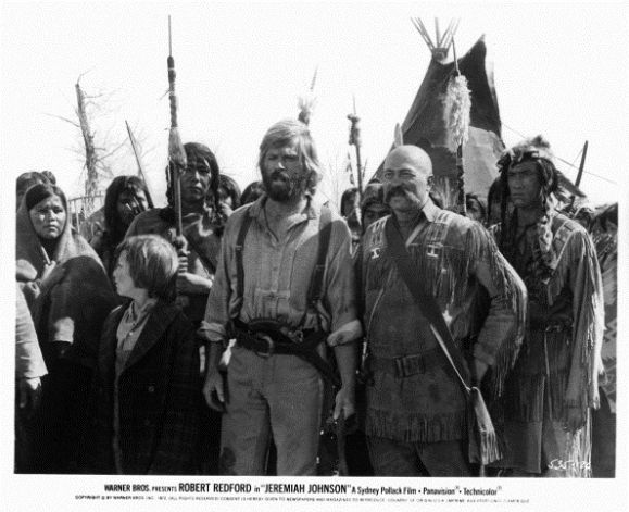 Josh Albee and Robert Redford standing with tribe of Indians in a scene from the film 'Jeremiah Johnson', 1972.