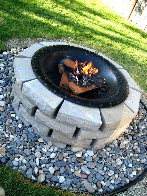 Great idea for an easy  DIY firepit.  Looks like they took the bowl of a commercially made firepit and simply set it on top of some stacked manufactured stone .  The rocks at the bottom add texture and color.  Vinyl border keeps the grass out.  This could probably be built in an hour.