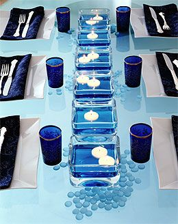 A pretty blue table setting for a dinner party.  Square clear dishes with water and a drop or two of blue food coloring, float a couple of candles, and add blue glasses and napkins.- Can change the color for any party