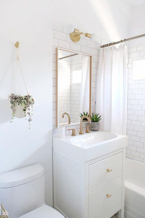 Small white bathroom features an Ikea Yddingen Washstand donning Lewis Dolin Round Bar Pulls in Brushed Brass and a white porcelain sink paired with a brass faucet placed under an Ikea Skogsvag Mirror mounted on white subway backsplash tiles lit by a by Cedar