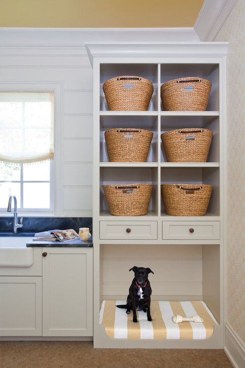 Fantastic cottage laundry room features white cabinets paired with soapstone countertops framing apron sink paired with gooseneck faucet and tongue and groove backsplash situated next to built-in shelves filled with woven laundry sorters stacked over built-in dog bed lined with white and yellow striped cushion atop terracotta hex tiled floor.