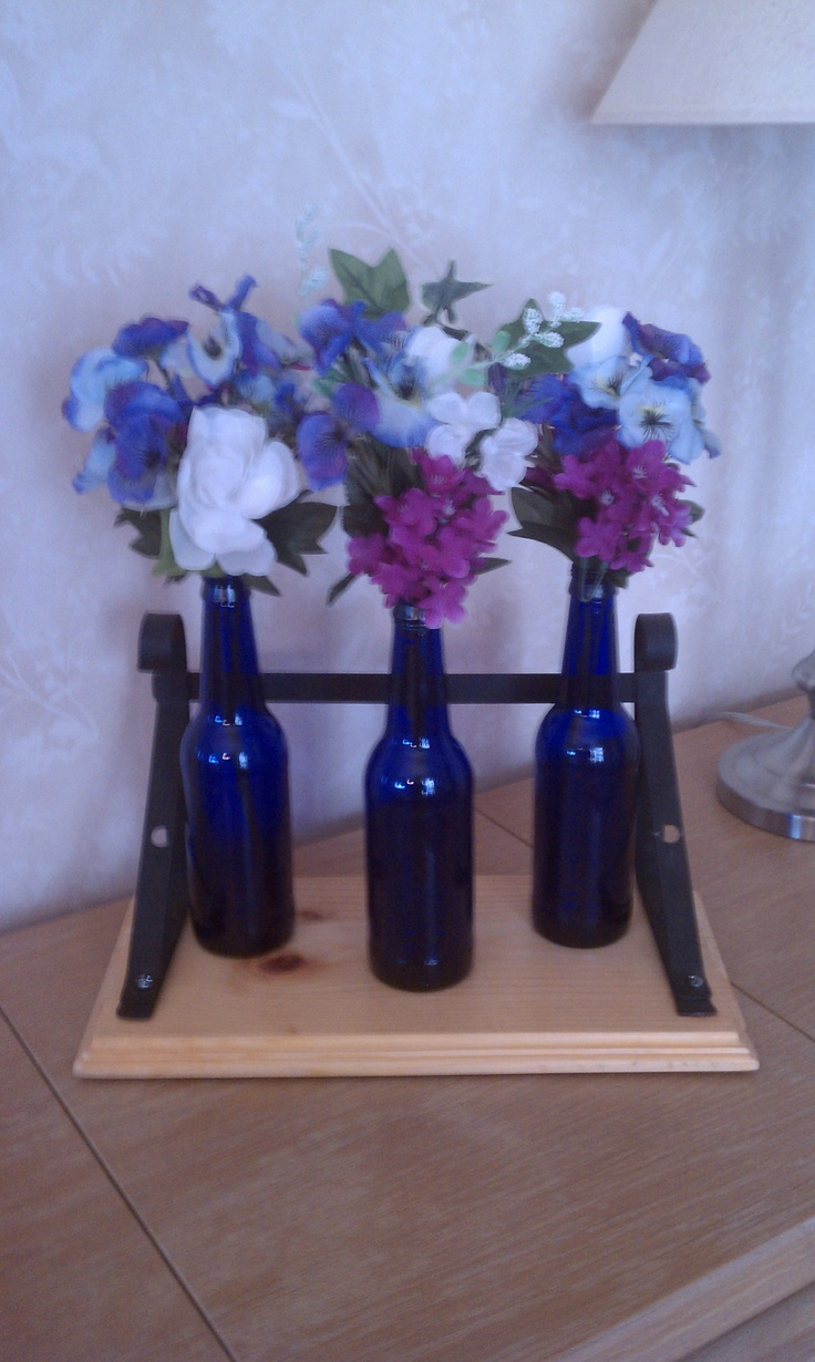 Recycled beer bottles with flowers and old wooden shelf for Beer bottle decoration ideas