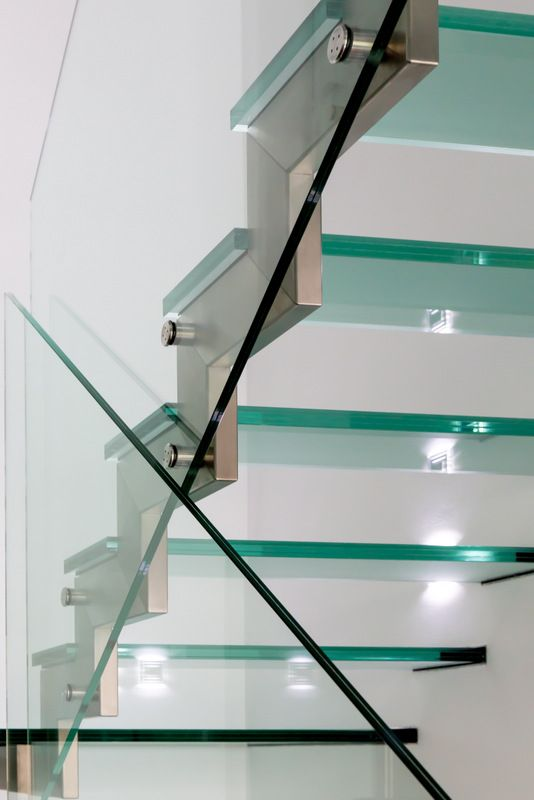Metal fixtures detail on glass steps and balustrade.