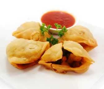CHICKEN SAMOSA. Fried pastry stuffed with chicken, peas & potatoes in curry flavor, served with BBQ sauce.
