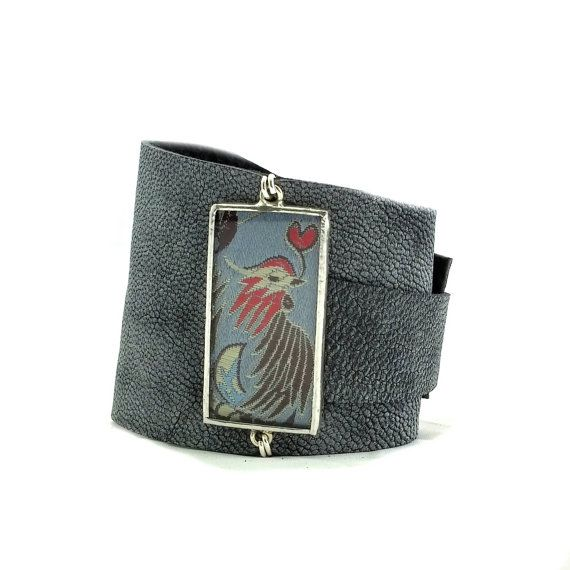 This cuff features the Chinese brocade pattern of a hen and heart on vivid grey silk, pressed under glass. The leather is soft and supple, and the image of the bird and heart is so sweet. You can choose to have us make a cuff that is just as featured in the picture, or you can select your own choice of fabric and leather. Please specify your preferences in a Note to Seller.  Each cuff is expandable and will fit any wrist measuring between 6 and 9 in circumfrence (15cm - 23cm). The width of…