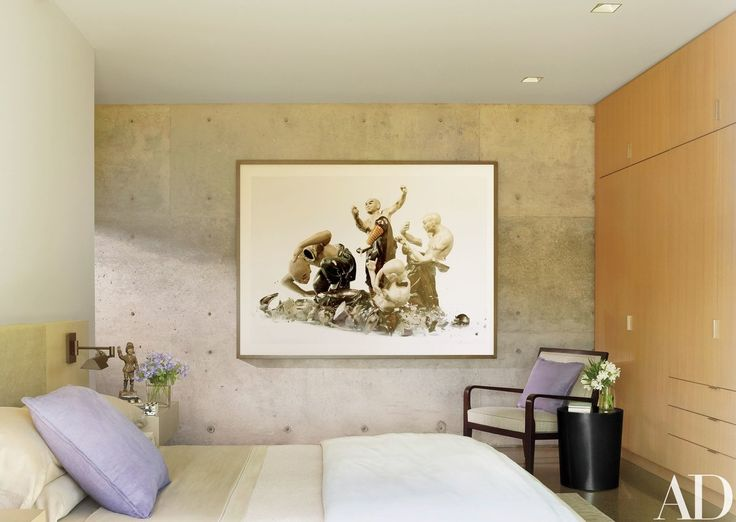 A photograph by Martin Klimas is displayed against a concrete wall in a bedroom; the chair is by Holly Hunt, the wall-mounted lamp is by Casella Lighting, and the bed linens are by Yves Delorme   archdigest.com