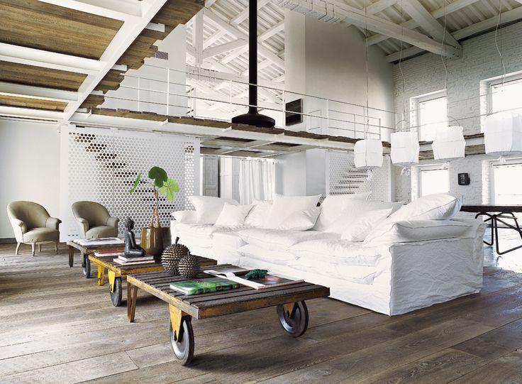 Una armónica composición formada por piezas de gran tamaño llena el amplio espacio de la casa. Carritos de tren hacen de mesas de centro; el sofá oversize con fundas blancas es un diseño de Paola Navone para Linteloo, y detrás, una gran mesa multiuso.