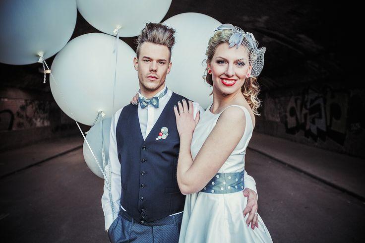modernes 50er Jahre Brautpaar mit rockabilly Brautkleid mit grauem Tüll, Fascinator mit grauen Knöpfen und Pünktchen und Federn