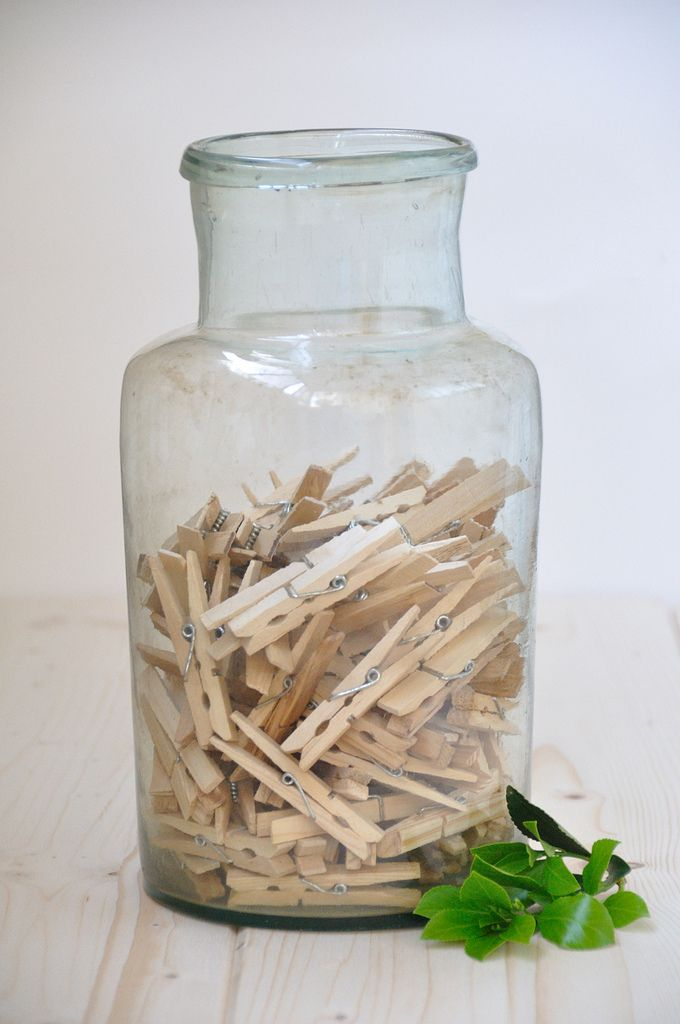 An antique pickling jar filled with wooden clothes pegs