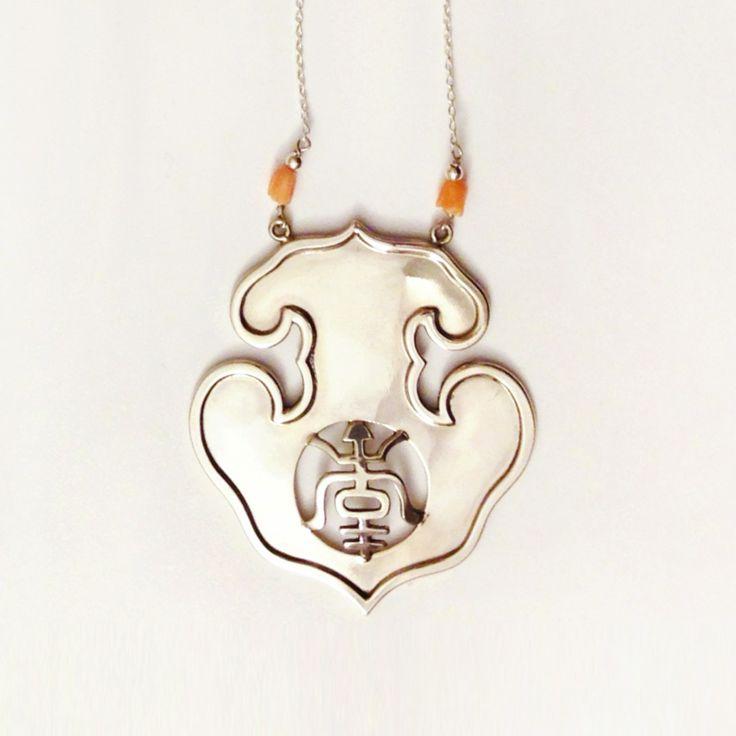 """Collana in argento ispirata alla forma dei gong cerimoniali di bronzo dei templi buddhisti estremo orientali, con all'interno il carattere """"longevità"""", montato con due piccoli fiori di corallo."""