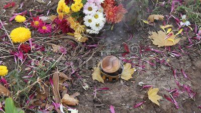 Smoldering incense on the grave and flowers.