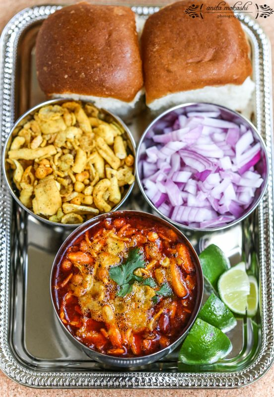 "Misal pav (spicy curry with bread – ""pav"") is a traditional Indian dish. It consists of spicy curry usually made of sprout of Mataki or white peas and chilly powder gravy called 'Kutt'. The final dish is topped with Potato-Chiwda Mix, Farsan or Sev), onions, lemon and coriander (cilantro). It is usually served with bread toasted with butter"