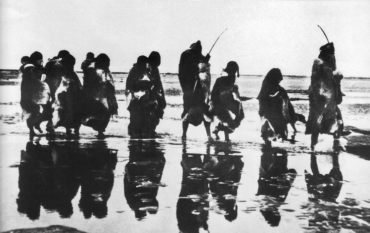 Grupo Selk-Nam caminando por la costa.  Foto: Charles W. Furlong, 1908.