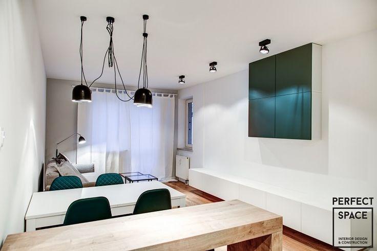Aranżacja salonu w nowoczesnym stylu. Białe ściany i meble ożywiają dodatki w kolorze butelkowej zieleni. Do tego duża ilość punktowego oświetlenia.