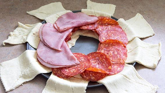 Crescent dough in a circle on a pizza pan topped with sliced ham and salami