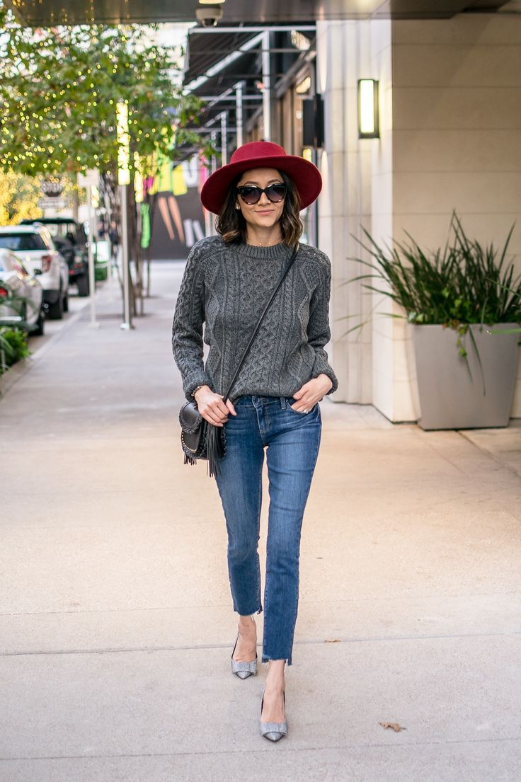 Cable knit sweater, raw hem jeans & red hat