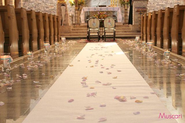 biały dywan obsypany płatkami róż i lampiony jako dekoracja kościoła podczas ślubu