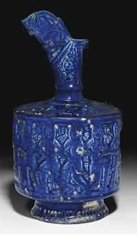 A Seljuk Ewer, decorated with dancing figures with linked arms, molded fritware with cobalt and turquoise glaze, Kashan, Central Iran, c. 1200, 32.3 cm high.