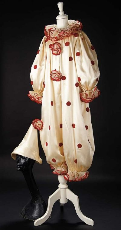 Love, Shirley Temple, Take Two: From Schoolgirl to Storybook: 44 Ivory Satin Clown Suit Worn by Shirley Temple - Of luxuriously draped ivory satin, the clown suit has red felt circle appliques and ruffled sheer collar, cuffs and pom-poms edged with red ribbon. There is a matching clown hat. The costume was worn by Shirley Temple at a mid-1930s birthday party for Darrilyn Zanuck. Z