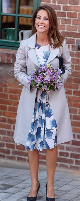 a stylish appearance in a floral dress and grey trench coat to open a ceramics factory in Denmark.