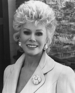 EVA GABOR 11 February 1919 – 4 July 1995) was a Hungarian-born American socialite and actress. She was widely known for her role on the 1965 to 1971 television sitcom Green Acres as Lisa Douglas, the wife of Eddie Albert's character, Oliver Wendell Douglas. She voiced Duchess in the 1970 Disney film The Aristocats, and Miss Bianca in Disney's The Rescuers and The Rescuers Down Under